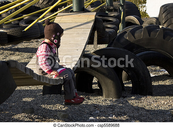Child sitting alone on a playground swing. - csp5589688