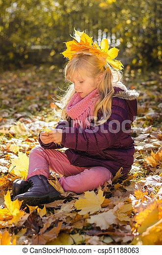 child sitting in autumn park - csp51188063