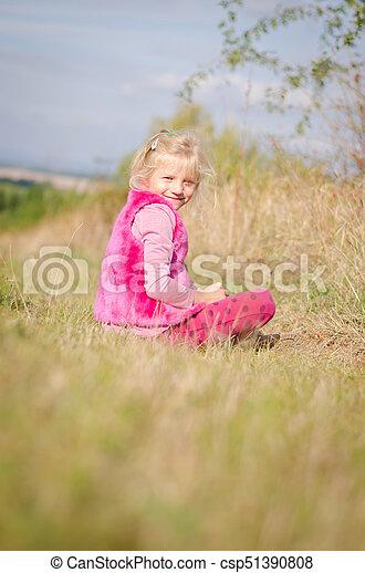 child sitting in grass - csp51390808