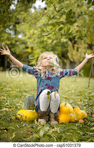 child throwing leaves in autumn time - csp51031379