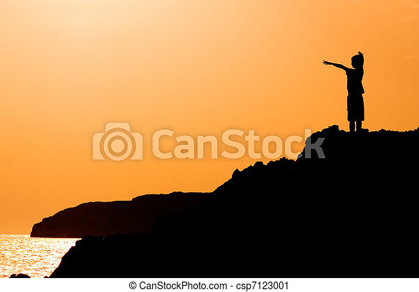 child with arms raised in joy at the vacation sunset - csp7123001