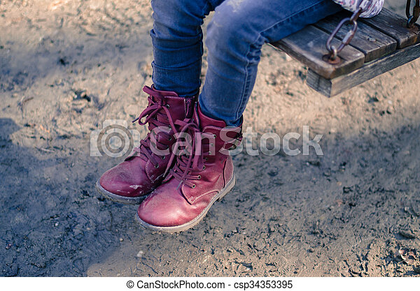 child with red shoes in swing - csp34353395