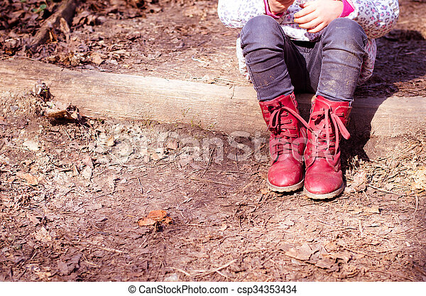 child with red shoes sitting and waiting - csp34353434