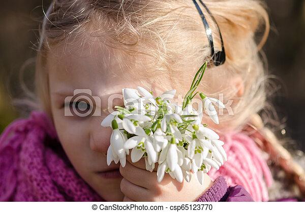 child with snowdrop flowers - csp65123770