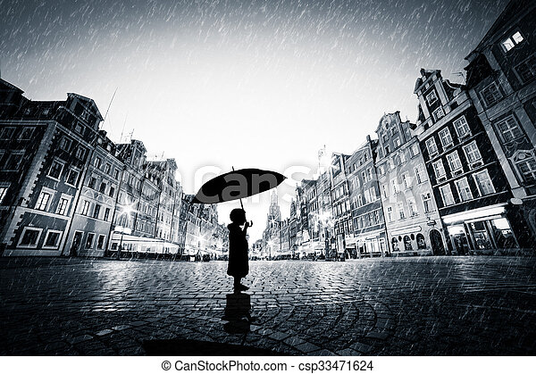Child with umbrella standing alone on cobblestone old town in rain - csp33471624