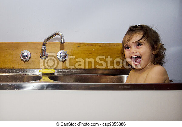 Childhood - bathing . Baby having a bath in the kitchen sink.