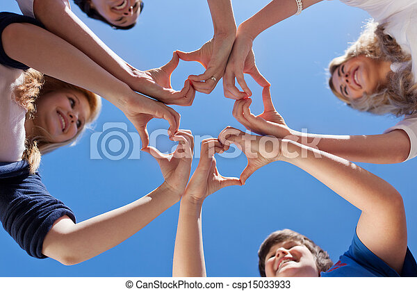 Children And Teacher Forming Hearts Against Blue Sky - csp15033933
