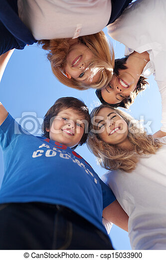 Children And Teacher Forming Huddle Against Clear Blue Sky - csp15033900