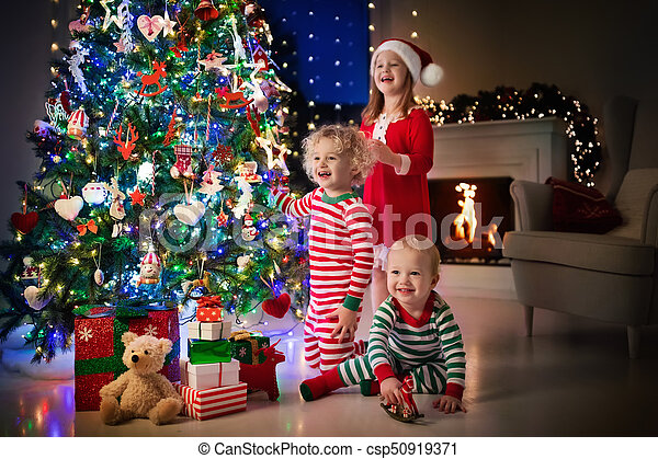 Children At Christmas Tree Kids At Fireplace On Xmas Eve Children At Christmas Tree And Fireplace On Xmas Eve Family With
