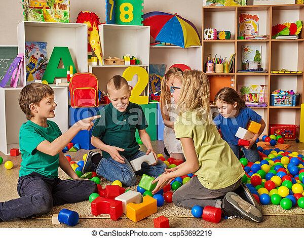 Children building blocks in kindergarten. Group kids playing toy floor . - csp53692219