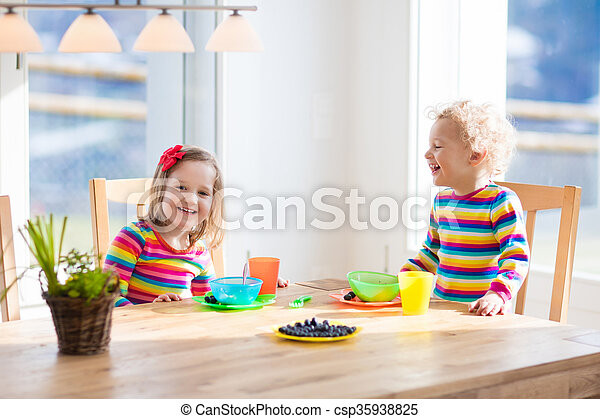 Children having breakfast in sunny kitchen - csp35938825