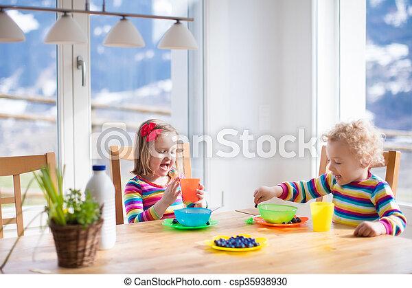 Children having breakfast in sunny kitchen - csp35938930