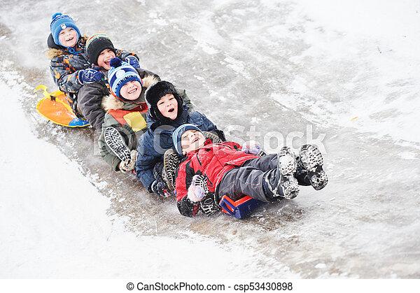 children having fun riding ice slide in snow winter - csp53430898