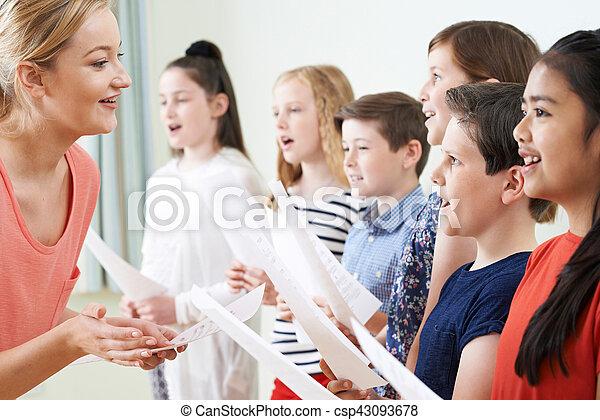 Children In School Choir Being Encouraged By Teacher - csp43093678