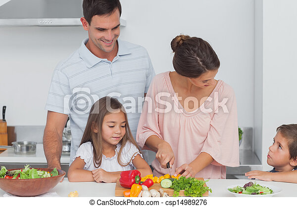 Children looking at their mother preparing vegetables - csp14989276
