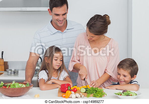 Children looking at their mother who is preparing vegetables - csp14989277