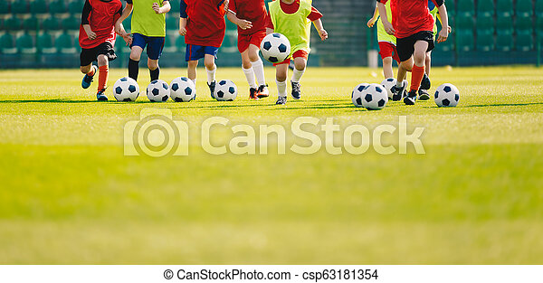 Children play soccer at grass sports field. Football training for kids. Children running and kicking soccer balls at soccer pitch. Soccer background with copy space on the bottom - csp63181354