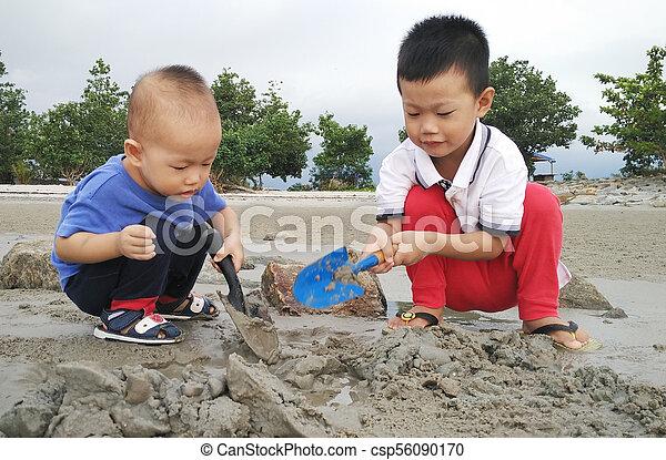 Children playing sand at beach - csp56090170