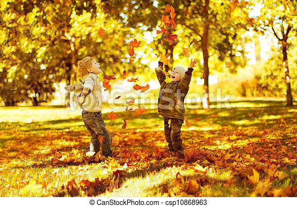 Children playing with autumn fallen leaves in park - csp10868963