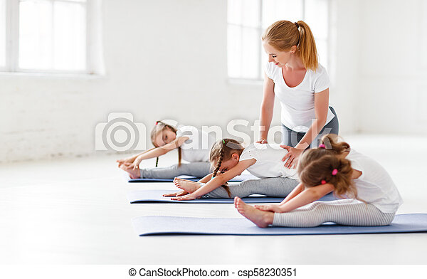 children practicing engaged in gymnastics and yoga with teacher - csp58230351
