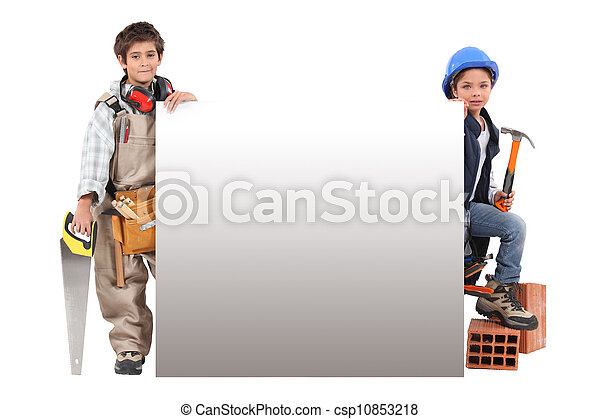 Children pretending to be construction workers standing around a blank sign - csp10853218