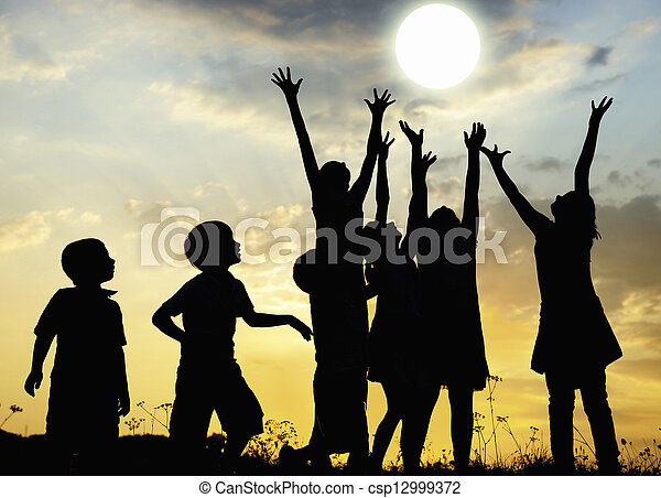 Children rising arms to sun on meadow - csp12999372