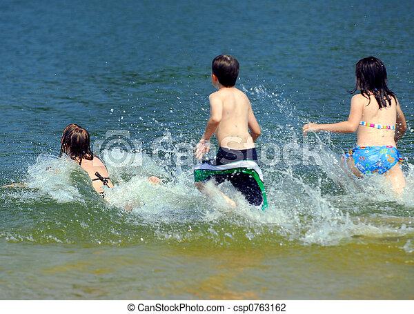 Children running into water - csp0763162