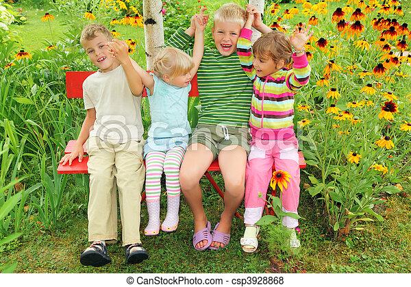Children sitting on bench in garden, having joined hands - csp3928868