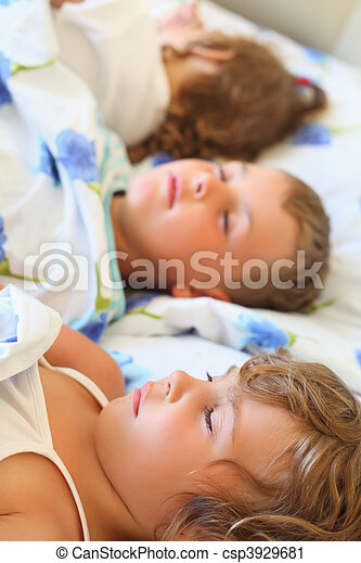 children three together sleeping on bed in cosy room, lying on back - csp3929681