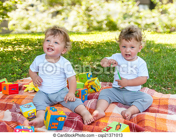 children twins sitting on a blanket among the toys in nature - csp21371013