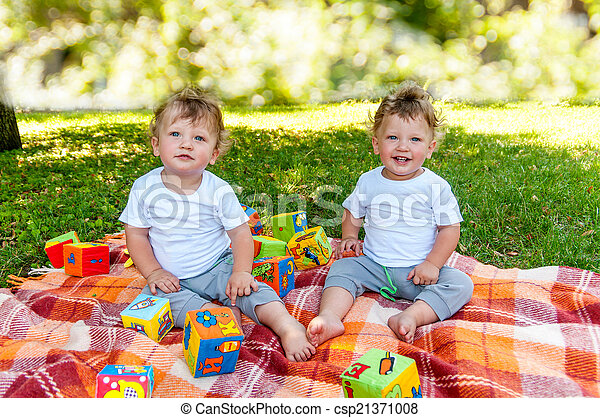 children twins sitting on a blanket among the toys in nature - csp21371008