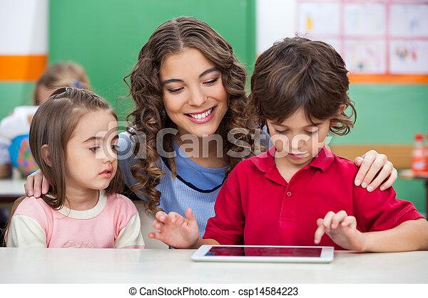 Children Using Digital Tablet With Teacher - csp14584223
