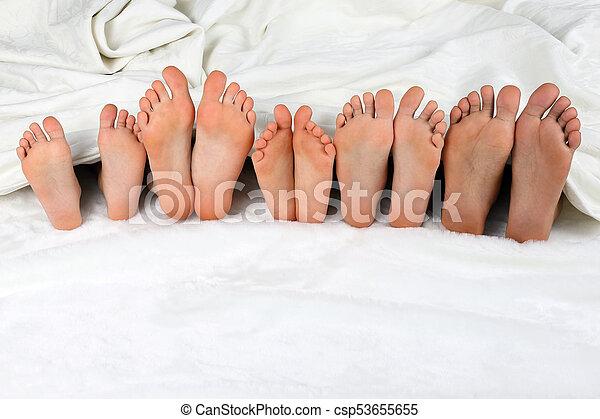 Childrens Feet Peeking From Under The Blanket