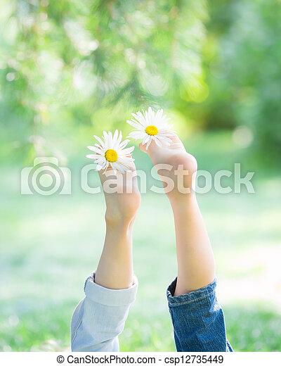 Children`s feet with flowers - csp12735449
