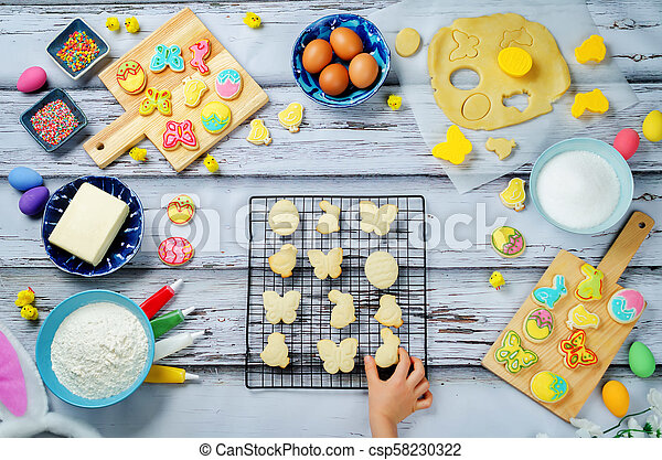 Child's hand with Sugar Easter cookies and ingredients for baking - csp58230322