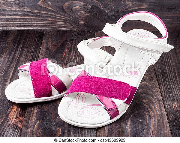child's sandals on a dark wooden background - csp43603923