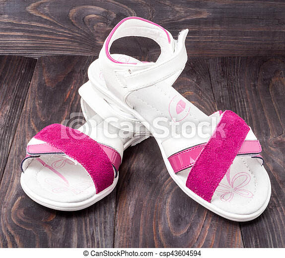 child's sandals on a dark wooden background - csp43604594