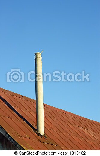 Chimney on an old tinny roof - csp11315462