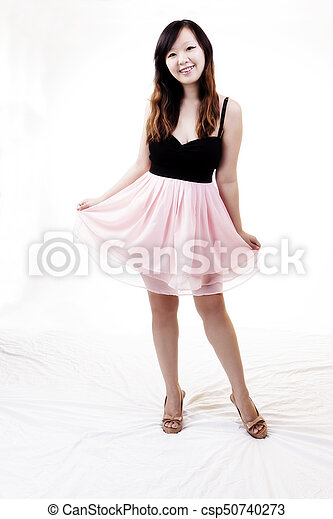 Chinese American Woman Standing In Pink And Black Dress - csp50740273