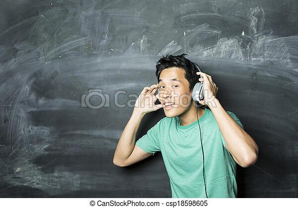Chinese man wearing earphones in front of a blackboard. - csp18598605