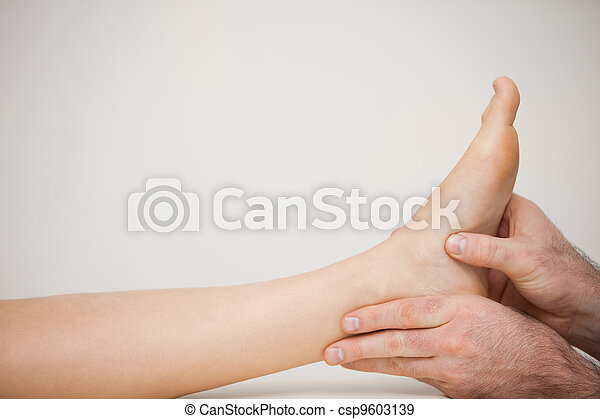 Chiropodist examining the foot of a patient - csp9603139