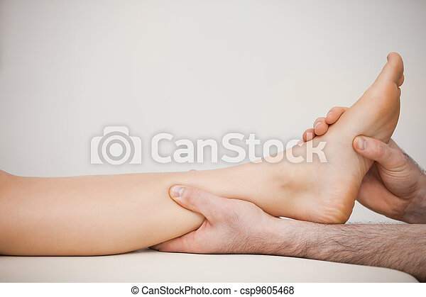 Chiropodist holding the calf of a patient - csp9605468