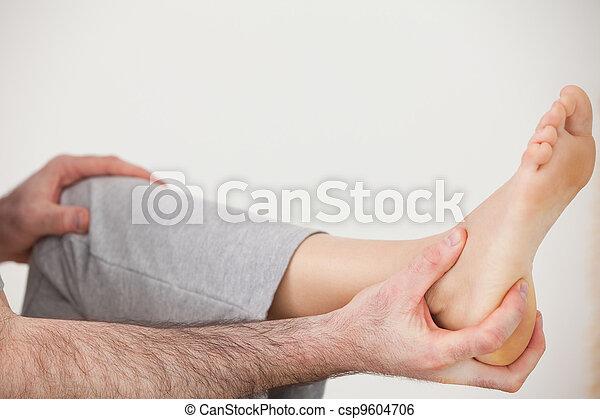 Chiropractor holding the heel of a patient - csp9604706