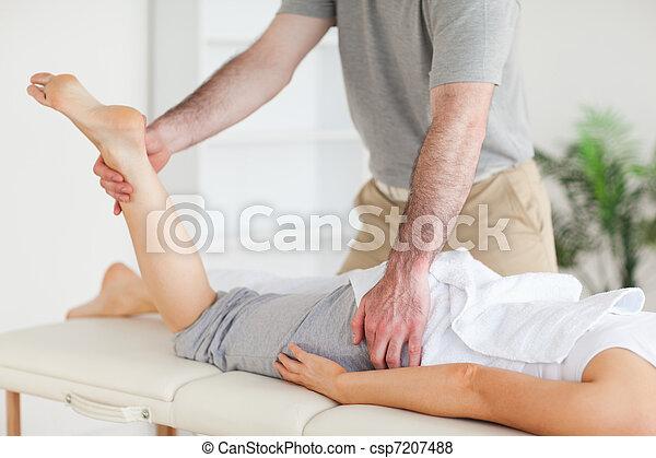 Chiropractor stretches a female customer's leg - csp7207488