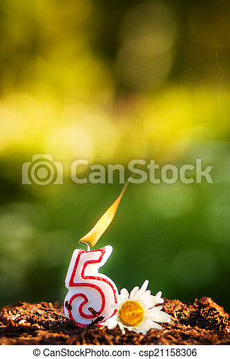 Chocolate cake with a lit candle, 5 years anniversary. - csp21158306