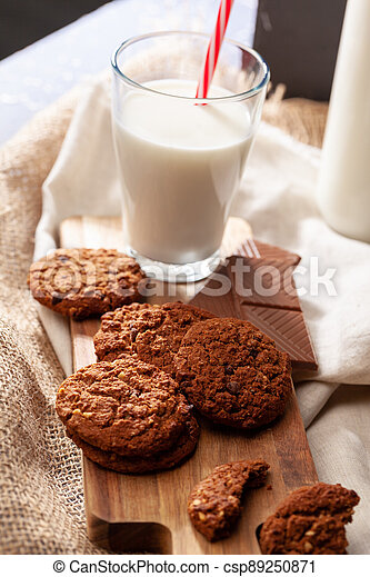 Chocolate crispy cookies with glass of milk close up - csp89250871