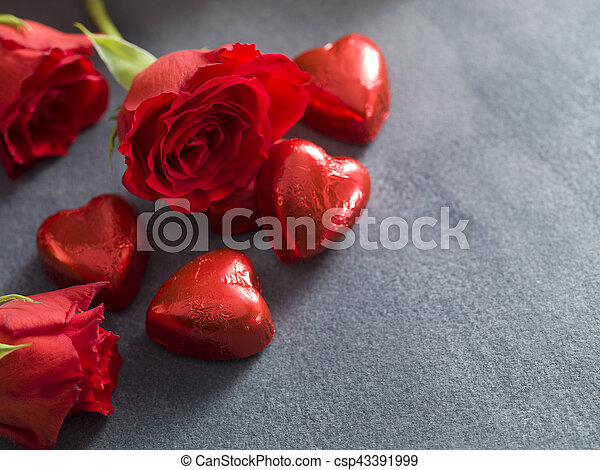 Chocolate hearts and red roses on a grey background - csp43391999