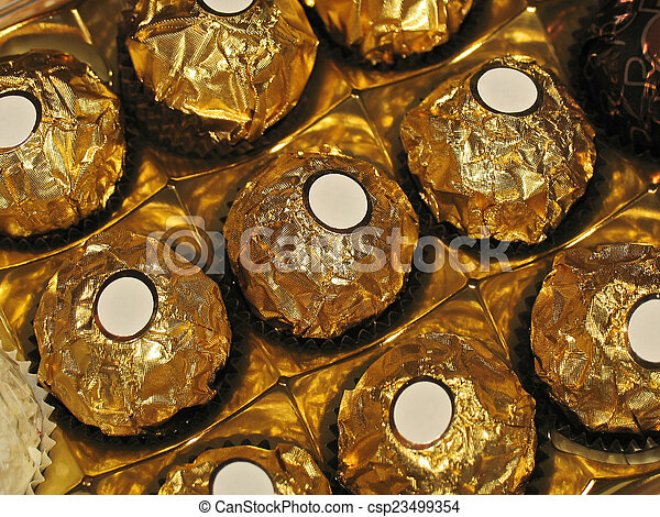 Chocolates with round shape in golden foil and white labels - csp23499354