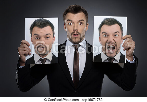 Choosing mask on today. Surprised young man in formalwear holding two photographs of himself expessing different emotions while isolated on grey - csp16671762
