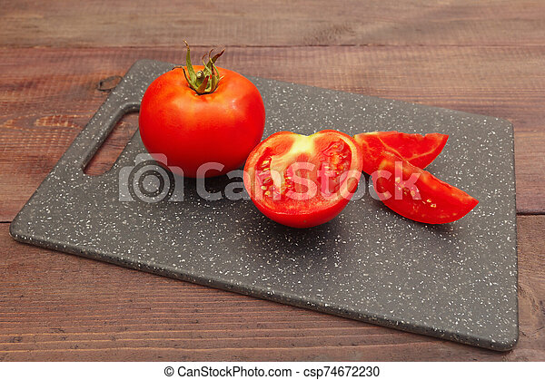 Chopped fresh tomato on cutting board on wooden table - csp74672230